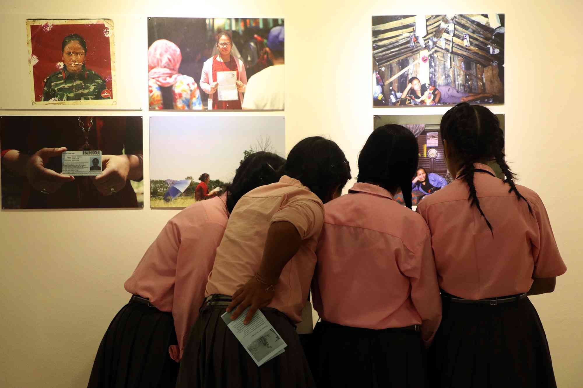 School children look at the photos of former women fighters of the Maoist army at the exhibition at the Nepal Art Council in Kathmandu. (Photo credit: Memory, Truth and Justice Exhibition 2018).