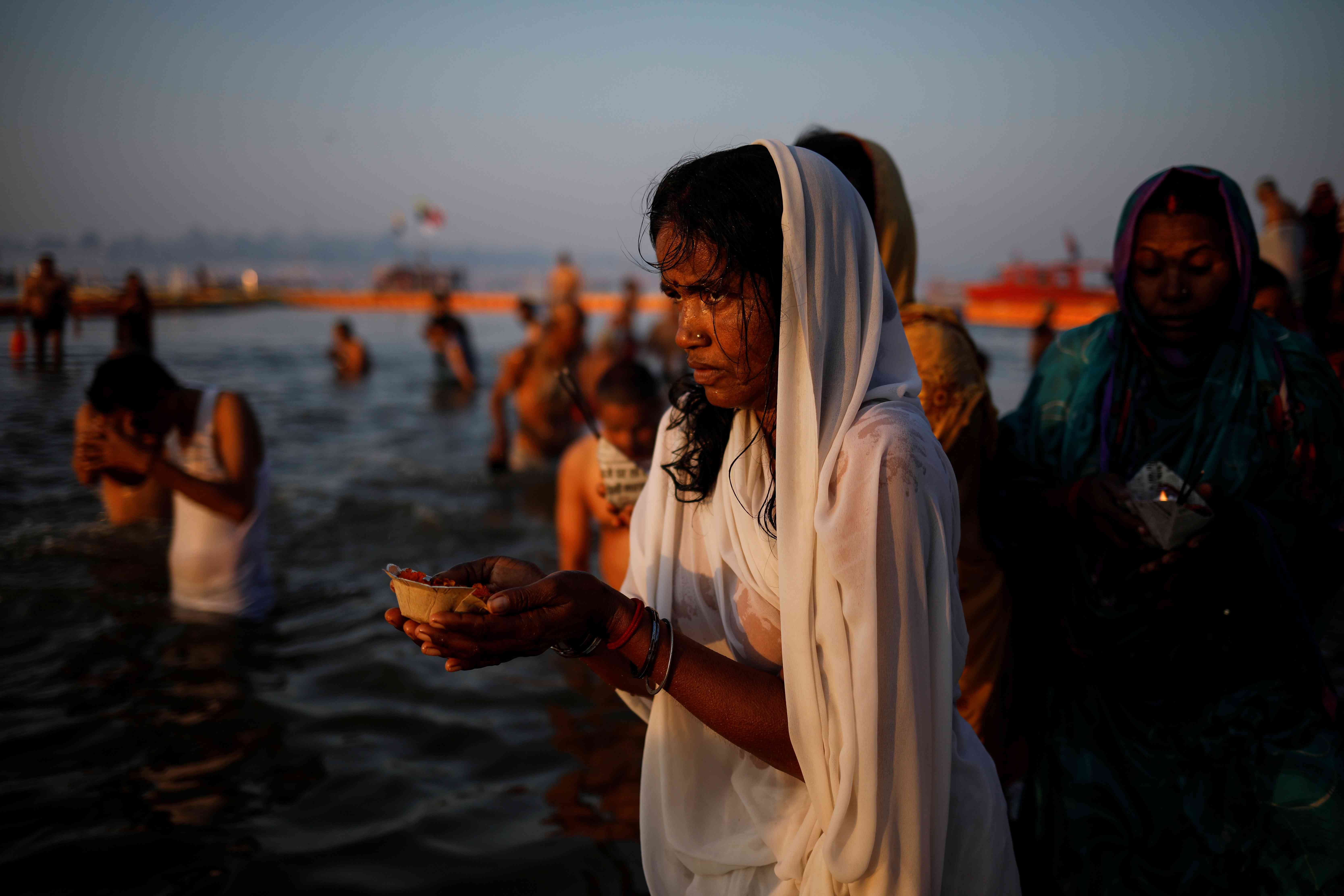 Hindu devotees pray after taking a holy dip during the Kumbh Mela. Photo credit: Reuters