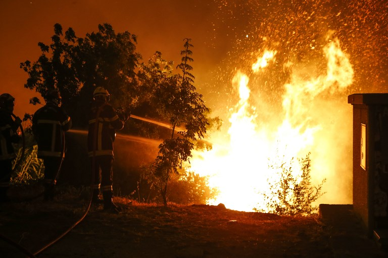 Firefighters try to douse the flames in Biguglia on the French Mediterranean island of Corsica. (Credit: Pascal Pochard-Casabianca/AFP)