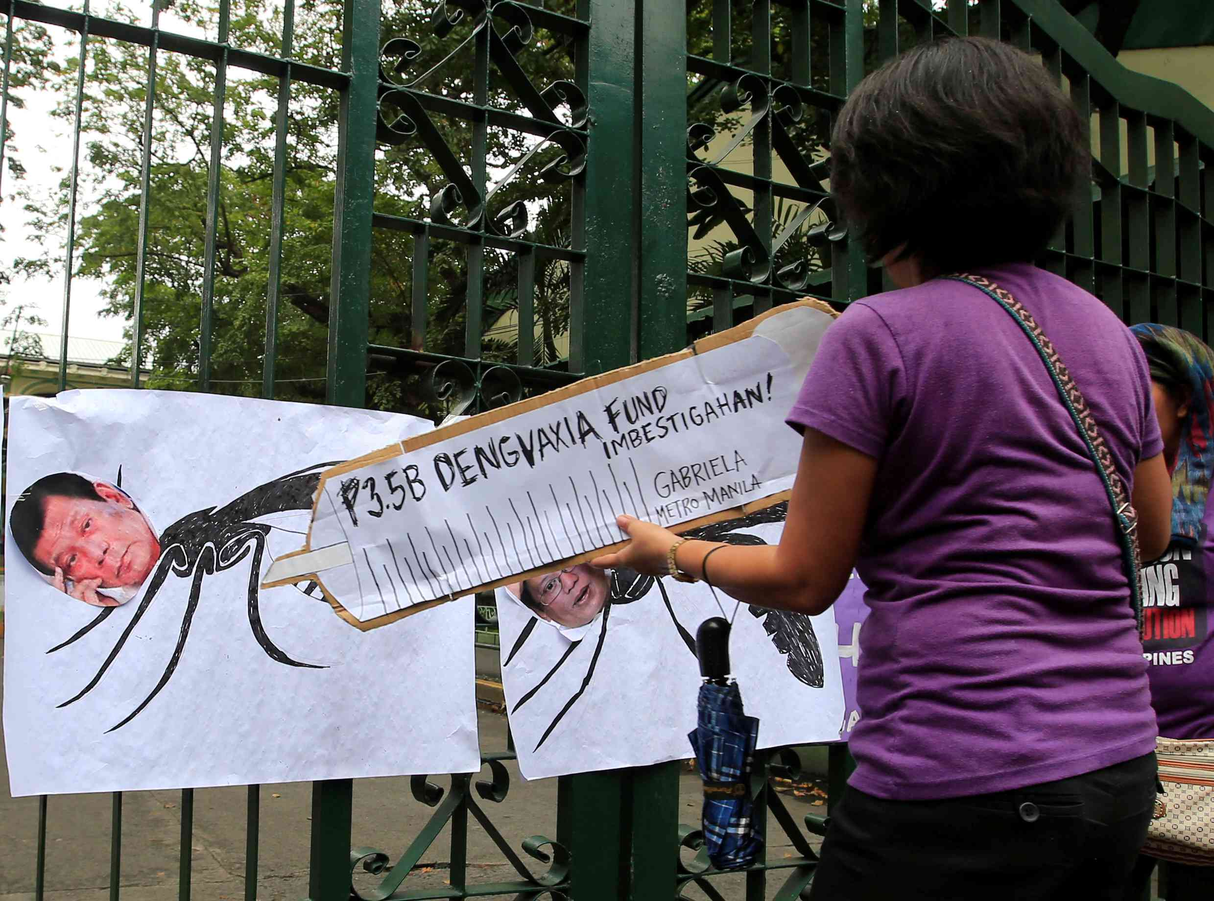 A demonstrator uses a mock syringe featuring the phrase '3.5 billion pesos Dengvaxia fund investigate' to point to a picture of President Rodrigo Duterte during a protest in front of the Philippine Department of Health in Manila in 2017. Photo credit: Reuters