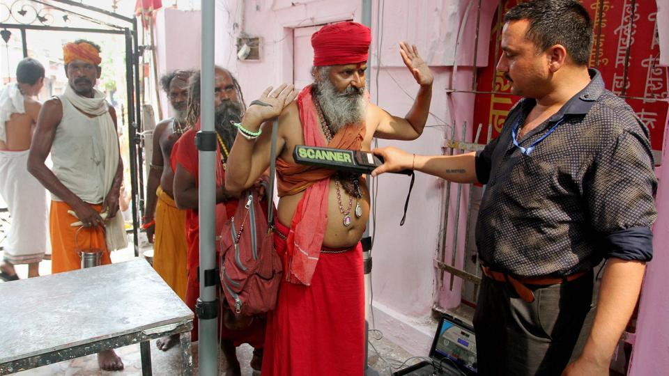 Sadhus undergo a security check before registering for the Amarnath Yatra in Jammu. (Photo credit: PTI).