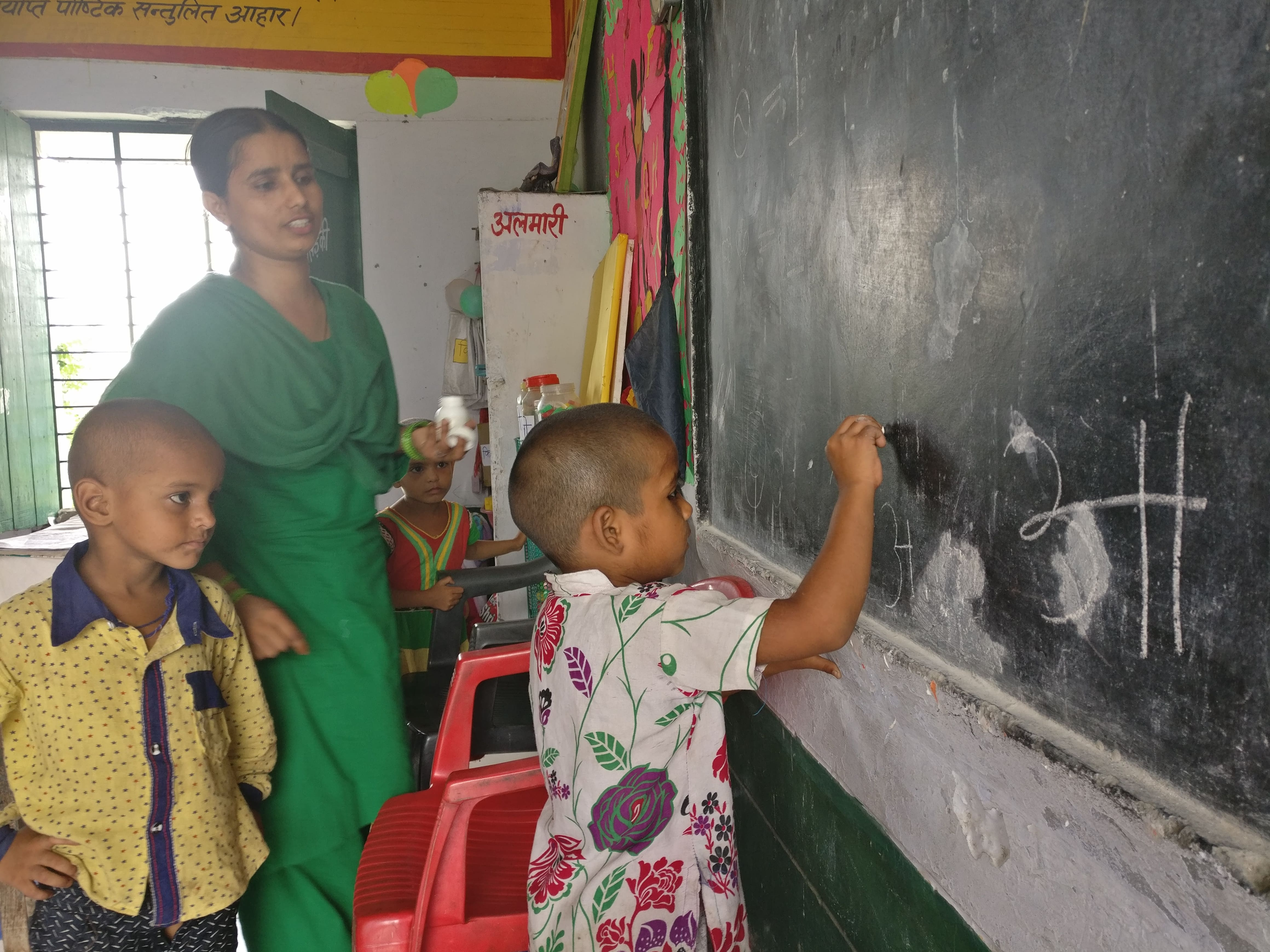Anganwadi worker Shabana Parveen watches Sophia, 5, write. Sophia only knows the first few letters of the Hindi alphabet. Photo credit: Shreya Roy Chowdhury