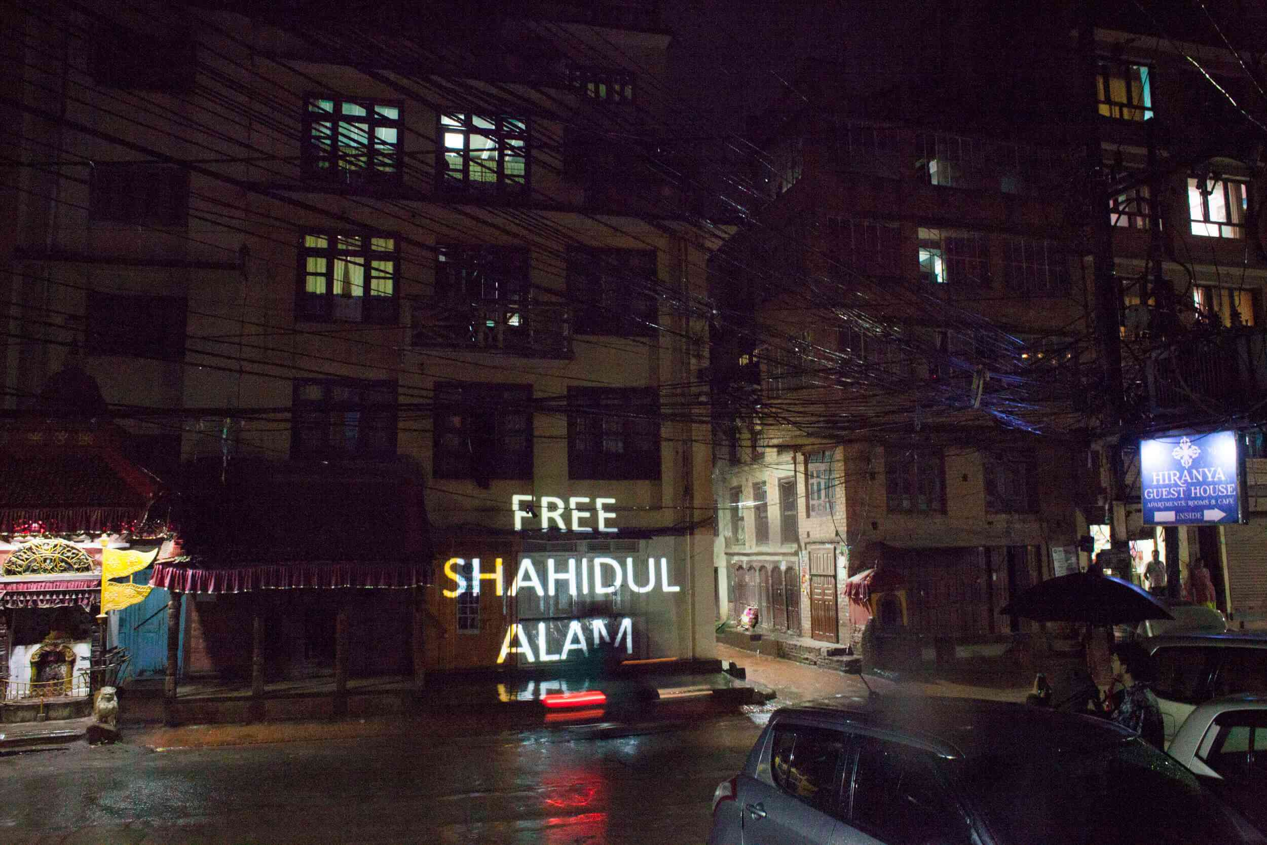 A 'Free Shahidul Alam' projection lights up a Kathmandu street at night during Sheikh Hasina's visit in August. (Credit: Photo Kathmandu)