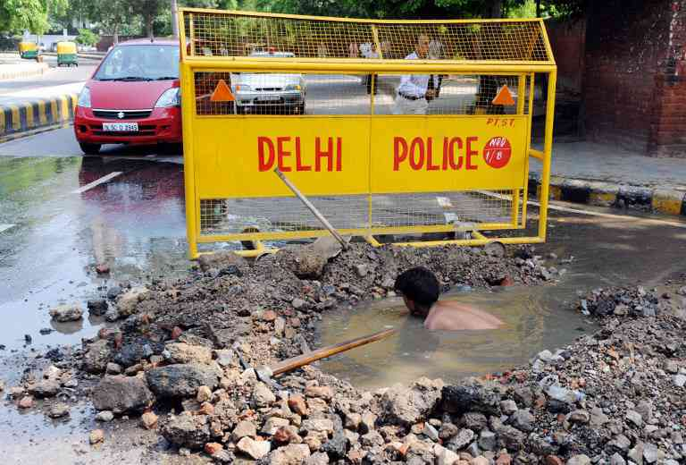 A municipal worker attempts to unblock a sewer in Delhi. To annihilate caste, reserve 100% jobs in sewer cleaning for the upper castes, says RJD MP Manoj Jha. (Photo credit: Raveendran/AFP).