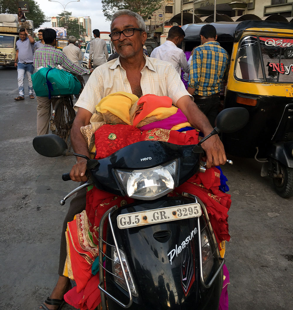 A small shopkeeper prepares to scooter back home with the stock he has just bought. Photo credit: M Rajshekhar