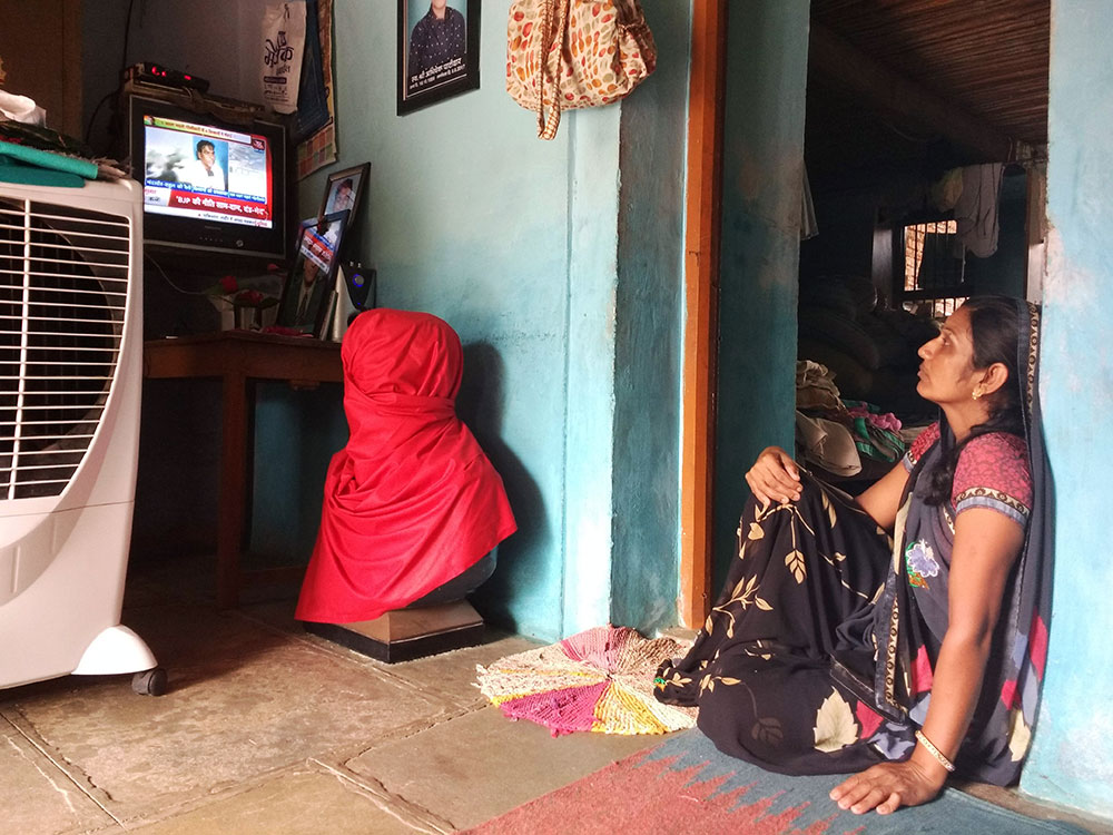 Alka Patidar watches a news report on Aaj Tak that features an interview with her and her husband that had been shot a few hours before. Covered in red cloth in the centre is a bust of her son Abhishek, which the family plans to unveil after June 10. Photo: Mridula Chari