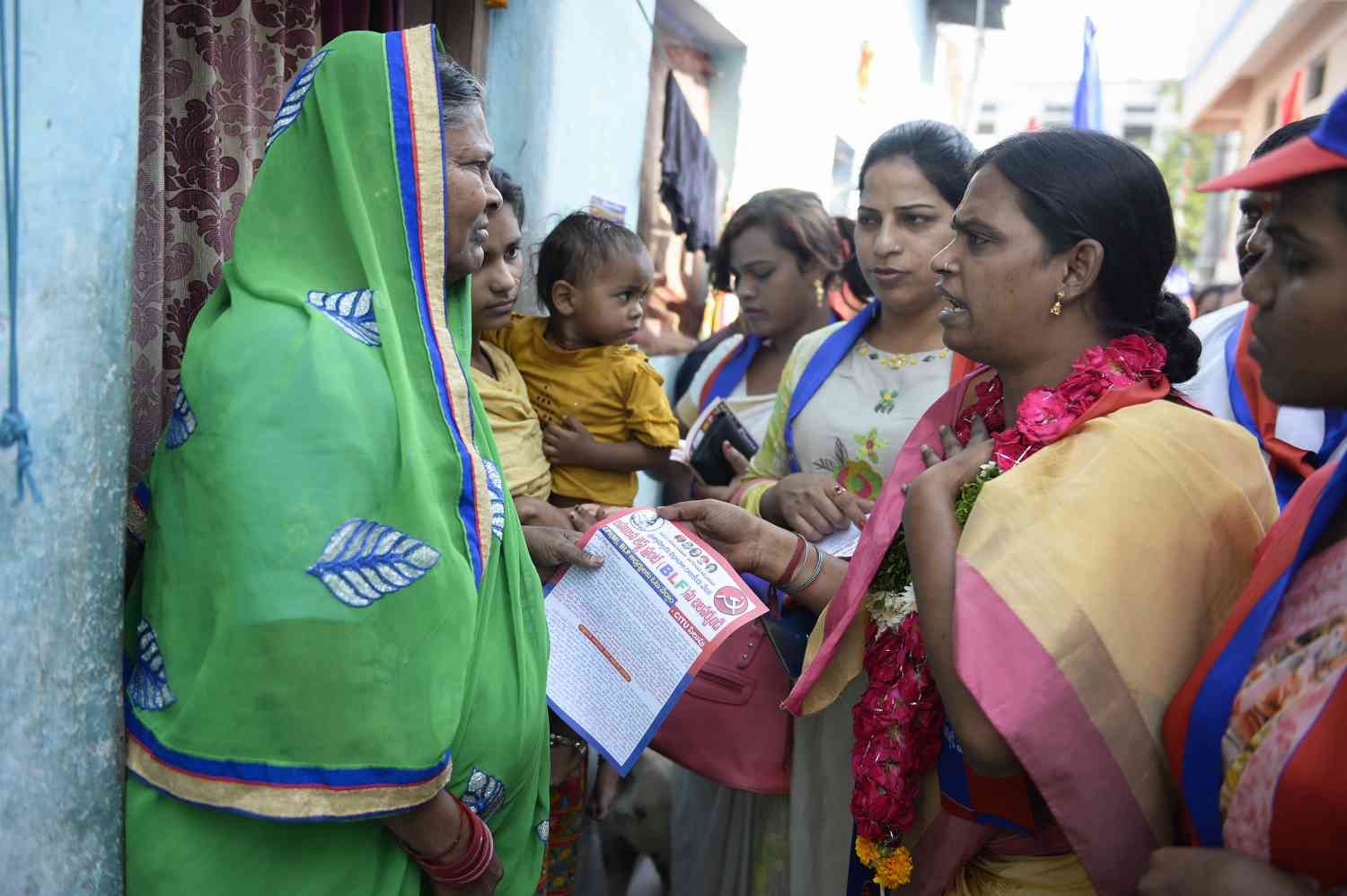 Chandramukhi Muvvala, 32, talks with voters as she campaigns in Hyderabad's Goshamahal constituency on November 26. She belongs to the Bahujan Left Front. (Photo credit: Noah Seelam/AFP).