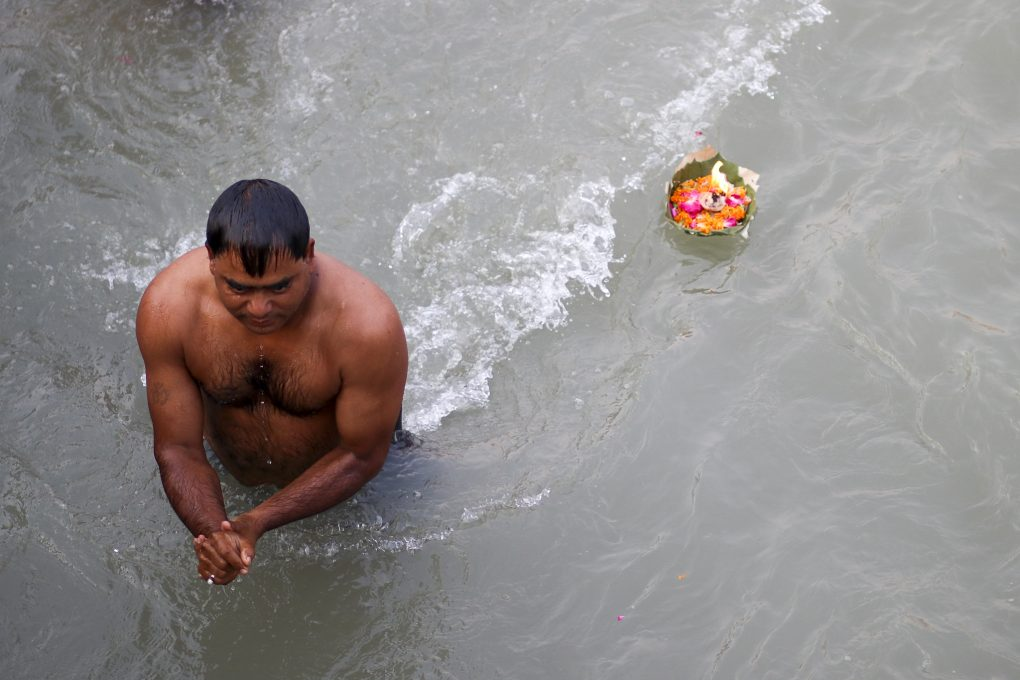 As a man takes a dip at Har Ki Pauri, devotional offerings disappear past him into the river.