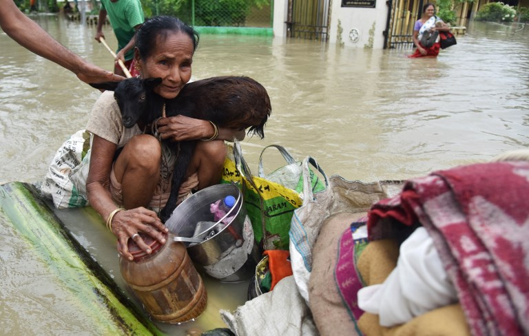 A woman holds a goat on a raft in the flood-affected Koliabor village in Assam. (Credit: Biju Boro/AFP)