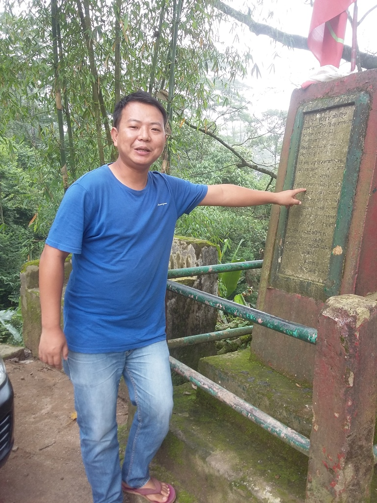 Salim Subba points at the names of martyrs inscribed on the memorial at the site of the June 1955 shootout. Photo credit: Anuradha Sharma.