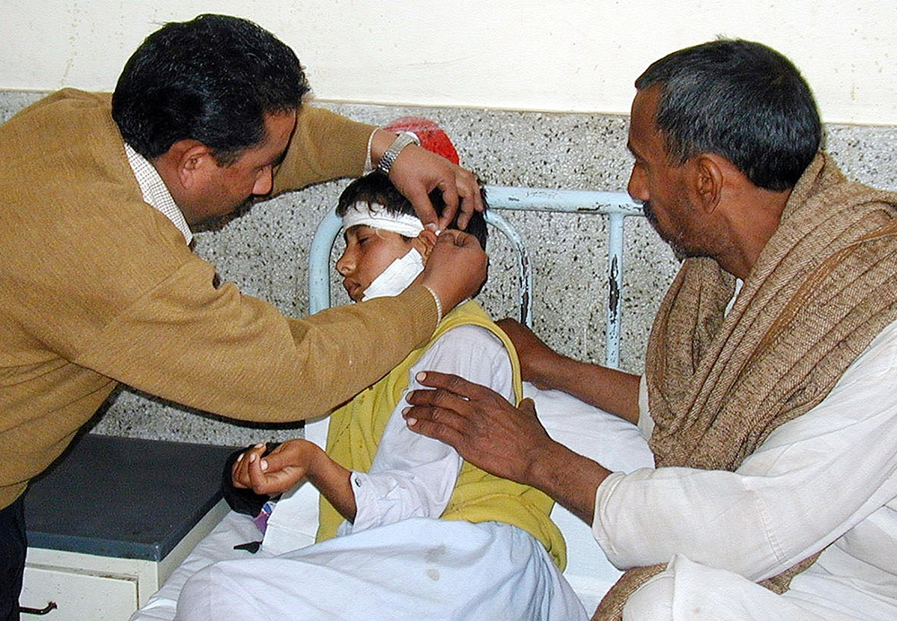 A paramedic treats Muhammad Raqeeb, who was wounded by Indian shelling in Nakyal sector, 250 kms south of Muzaffarabad, capital city of Pakistan-administered Kashmir, in February 2003. Credit: AFP