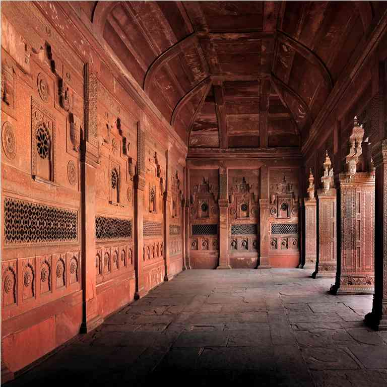Jahangiri Mahal: A sequence of interconnected chambers, some embellished with plaster walls, leads to the riverside court of the Jahangiri Mahal, that was built between 1565 and 1569, in Fatehpur Sikri. It is defined by apartments on three sides, that on the west presents a triple-bayed, double-height entrance framed by slender stone columns that imitate timber originals. These features contrast with the arched recesses at either side and with the arched portals flanked by similarly-shaped recesses leading to the apartments on the north and south. A small octagonal pool set into the middle of the court is fed by a narrow water channel. The eastern perimeter of the court consists of a line of jalis (latticed screen) that permit views across the river. The walls (as seen from below) are adorned with polychrome panels set between octagonal towers with chhatris, as on the frontal facade of the pala.