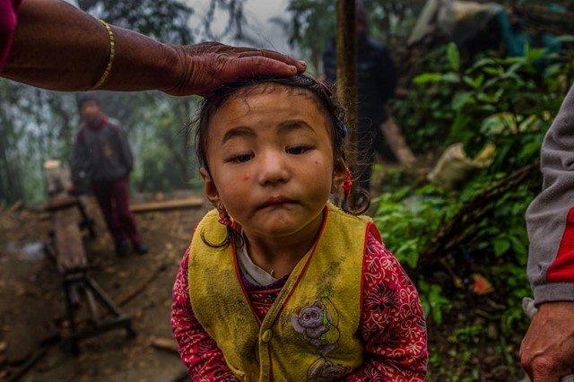 A child plays while her family builds their hut. Professional sherpas continue risking their lives so that their children can get good education.