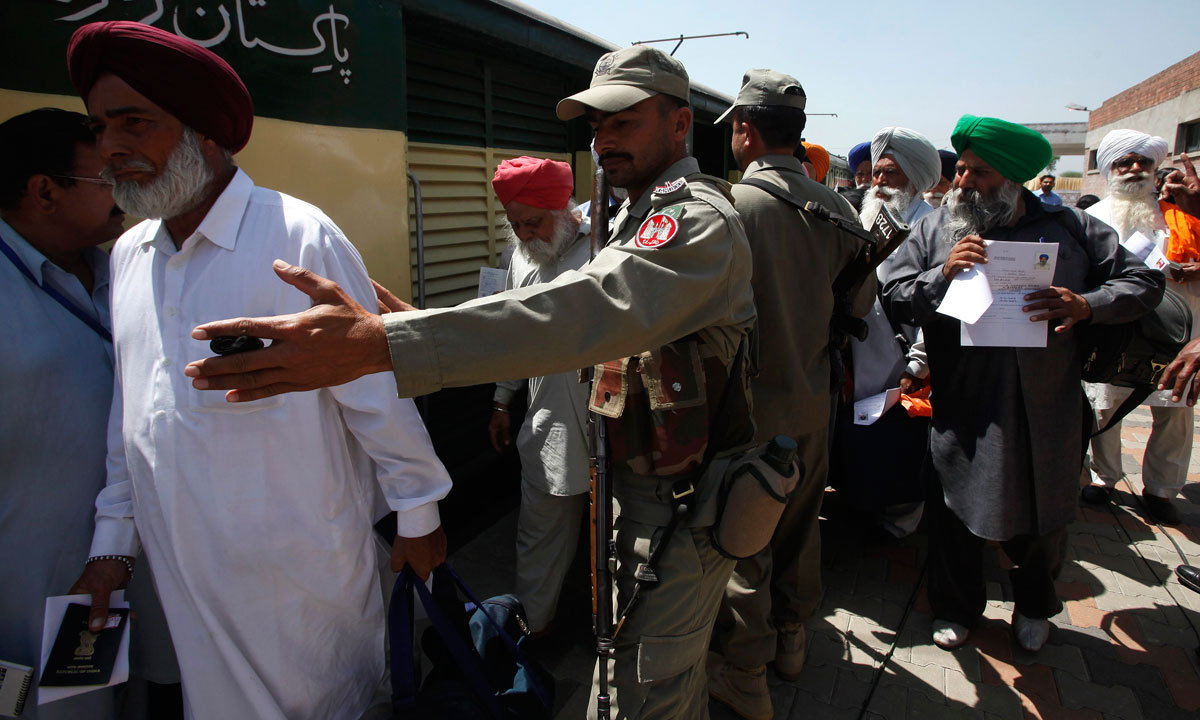 Paramilitary soldiers escort Indian Sikh pilgrims as they arrive at the Wagah border in Pakistan. (Credit: Reuters)