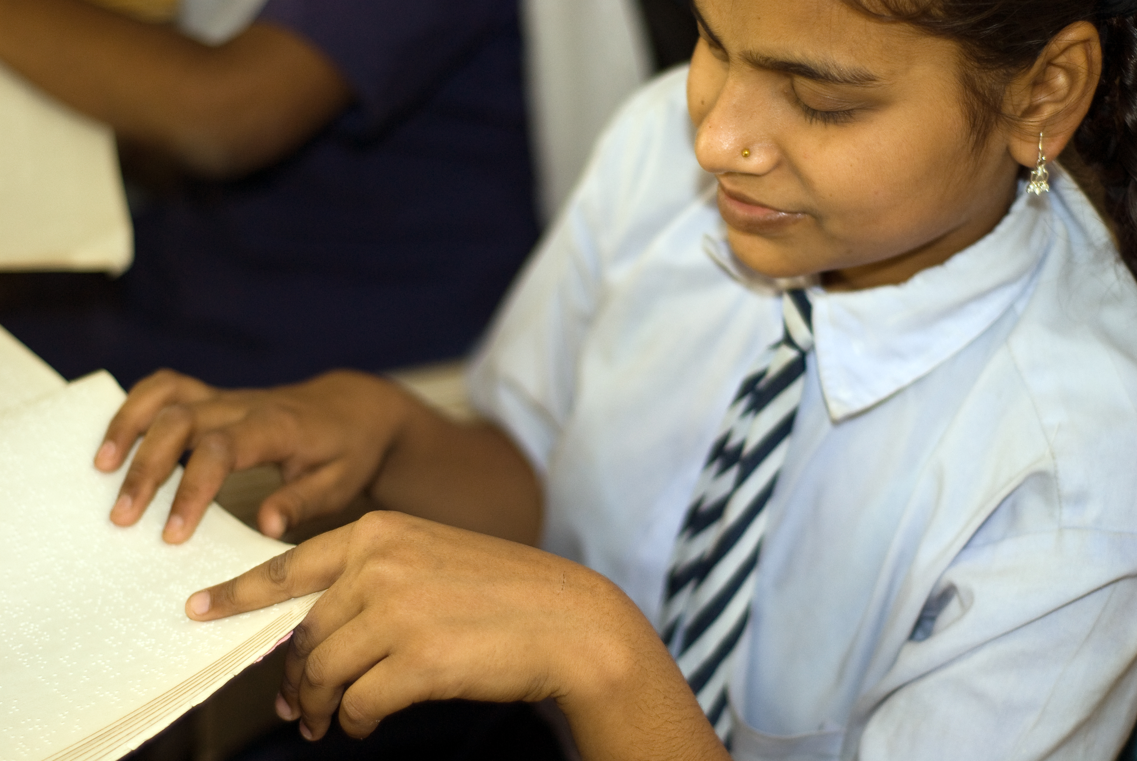 A girl reading braille at the Bihar Natraheen Parishad or Bihar School for Blind Girls. Photo credit: JP Davidson/Flickr [Licensed under CC BY 2.0]
