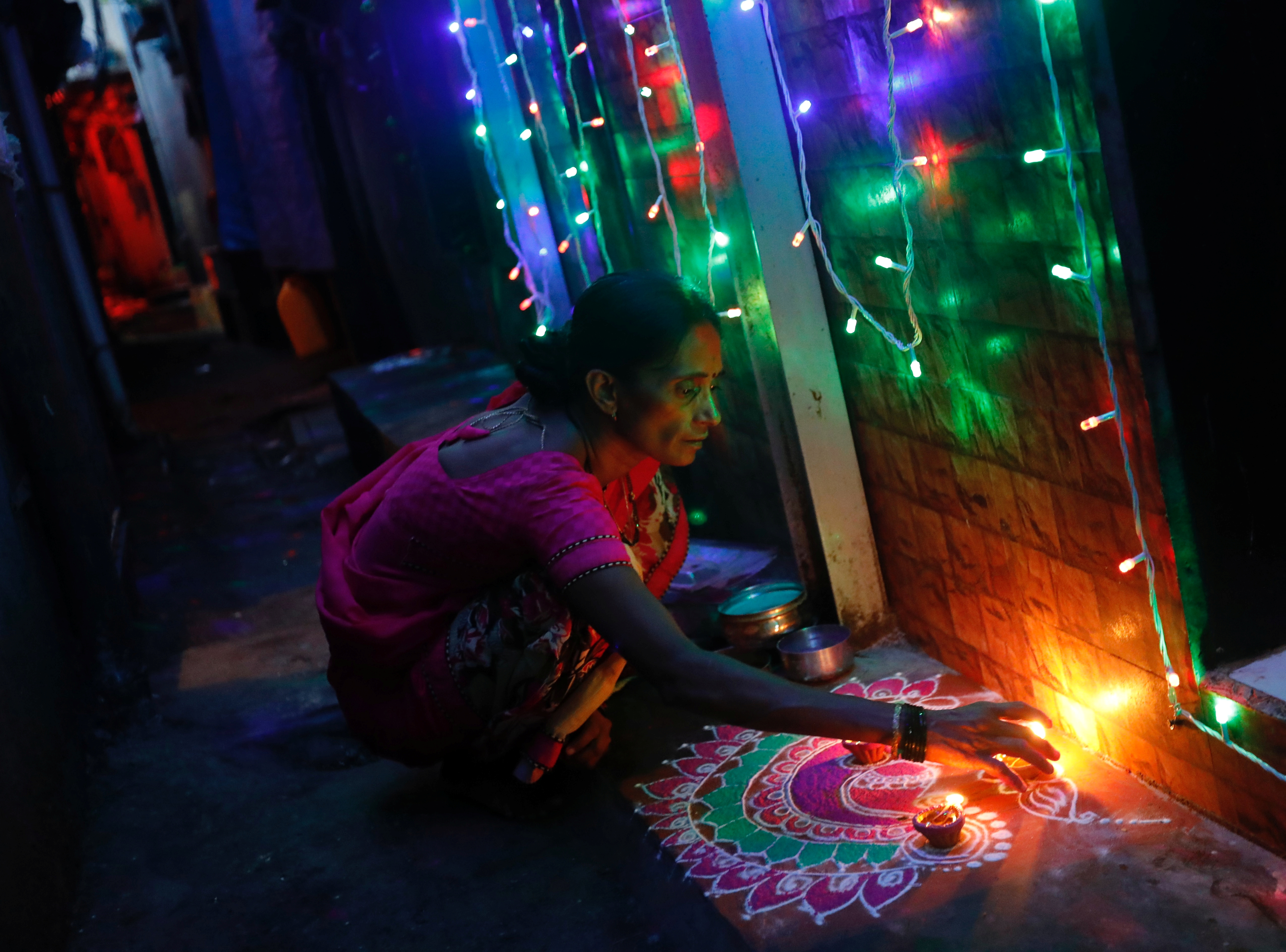 A woman decorates her house on the eve of Diwali in Mumbai. (Credit: Danish Siddiqui/Reuters)