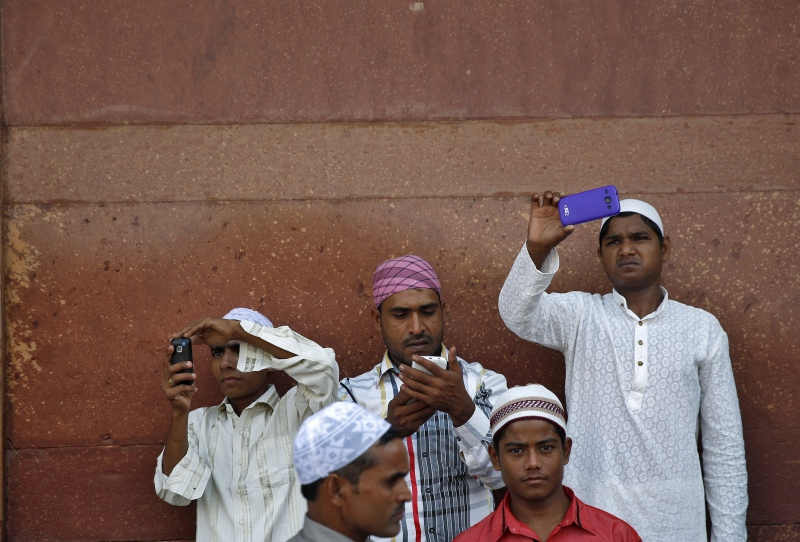 Muslims use their mobile phones after offering Eid prayers at the Jama Masjid in Old Delhi in 2014. (Photo credit: Reuters).