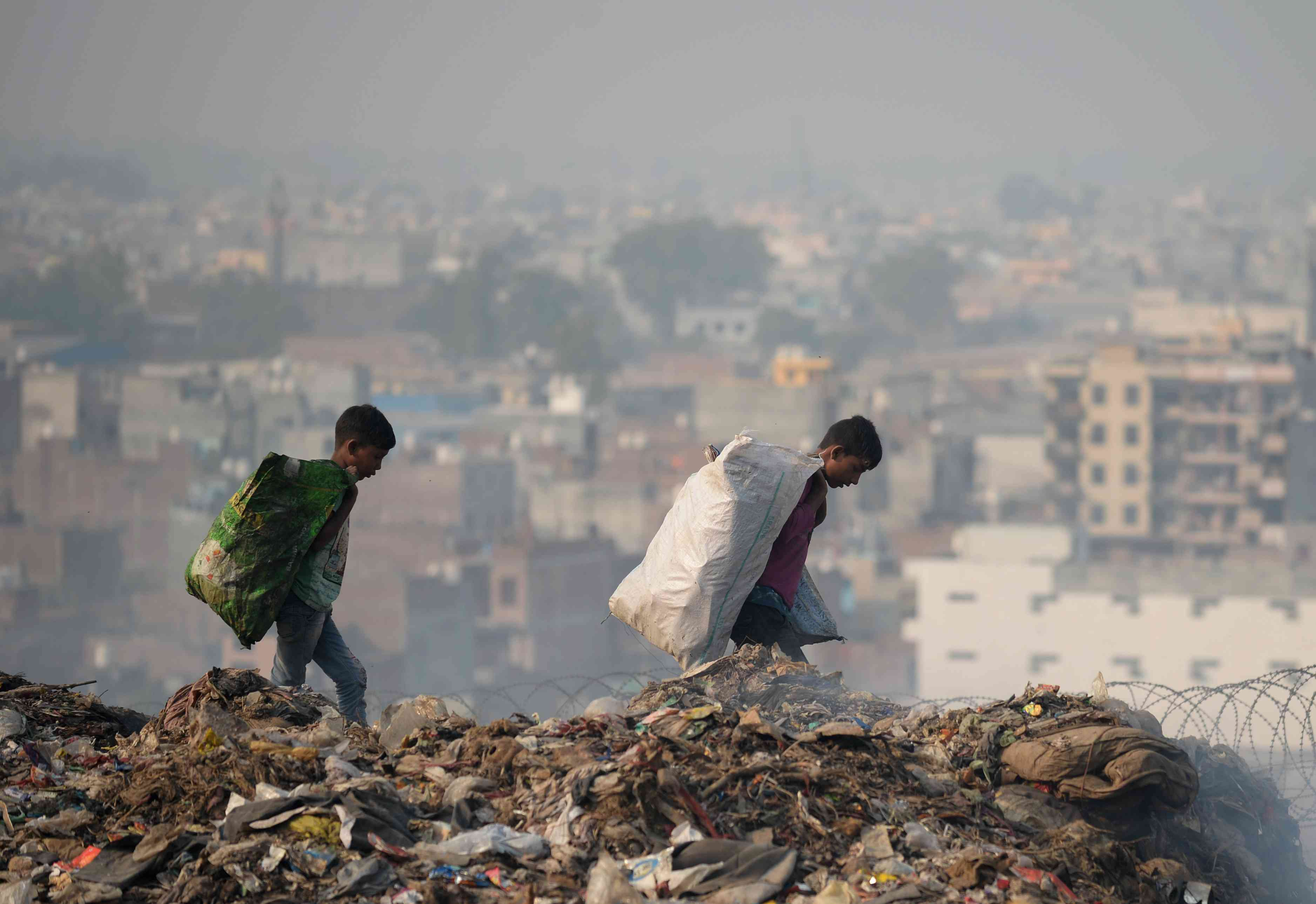 Ragpickers carry bags with usable items collected from a garbage dump at the Bhalswa landfill site in New Delhi on October 29. (Photo credit: Sajjad Hussain/AFP).