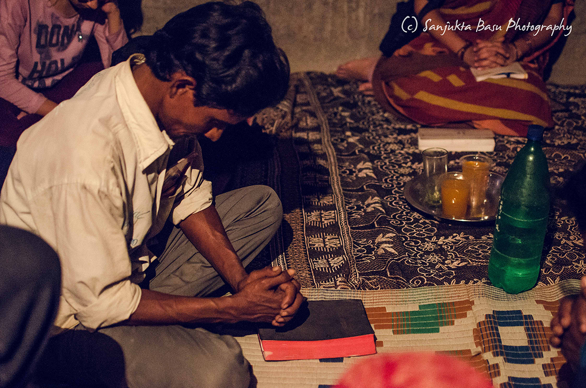 A Dalit member of Rajesh Naik's fellowship joins the Karwan team in praying for peace and truth. (Credit: Sanjukta Basu / Karwan e Mohabbat)