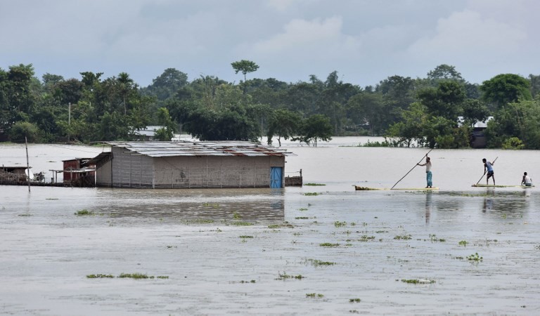 Villagers paddle their rafts near a partially submerged house in Tezpur, 170 km from Guwahati. (Credit: Biju Boro/AFP)