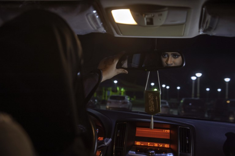 Sabika Habib adjusts the mirror of her car while she is on her way to Bahrain. (Credit: Hussain Radwan/AFP)