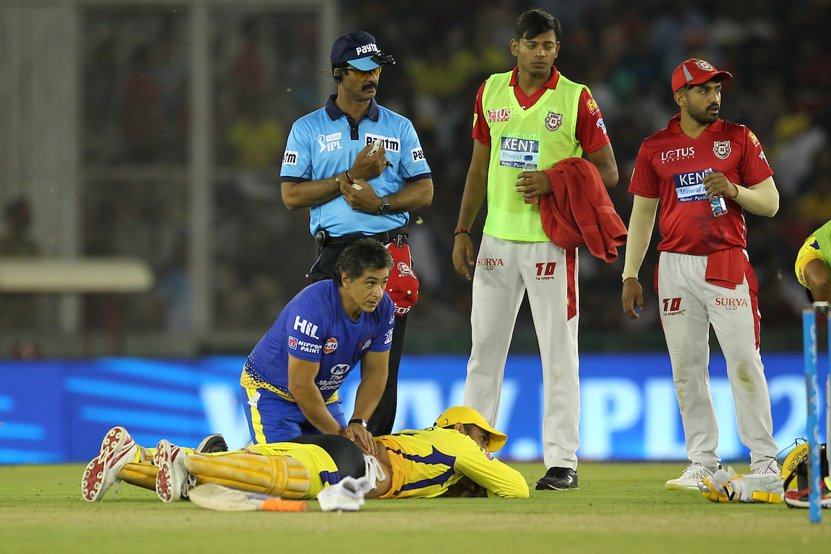 Dhoni getting treatment on the pitch after hurting his back | Image courtesy: Deepak Malik / IPL/ SPORTZPICS