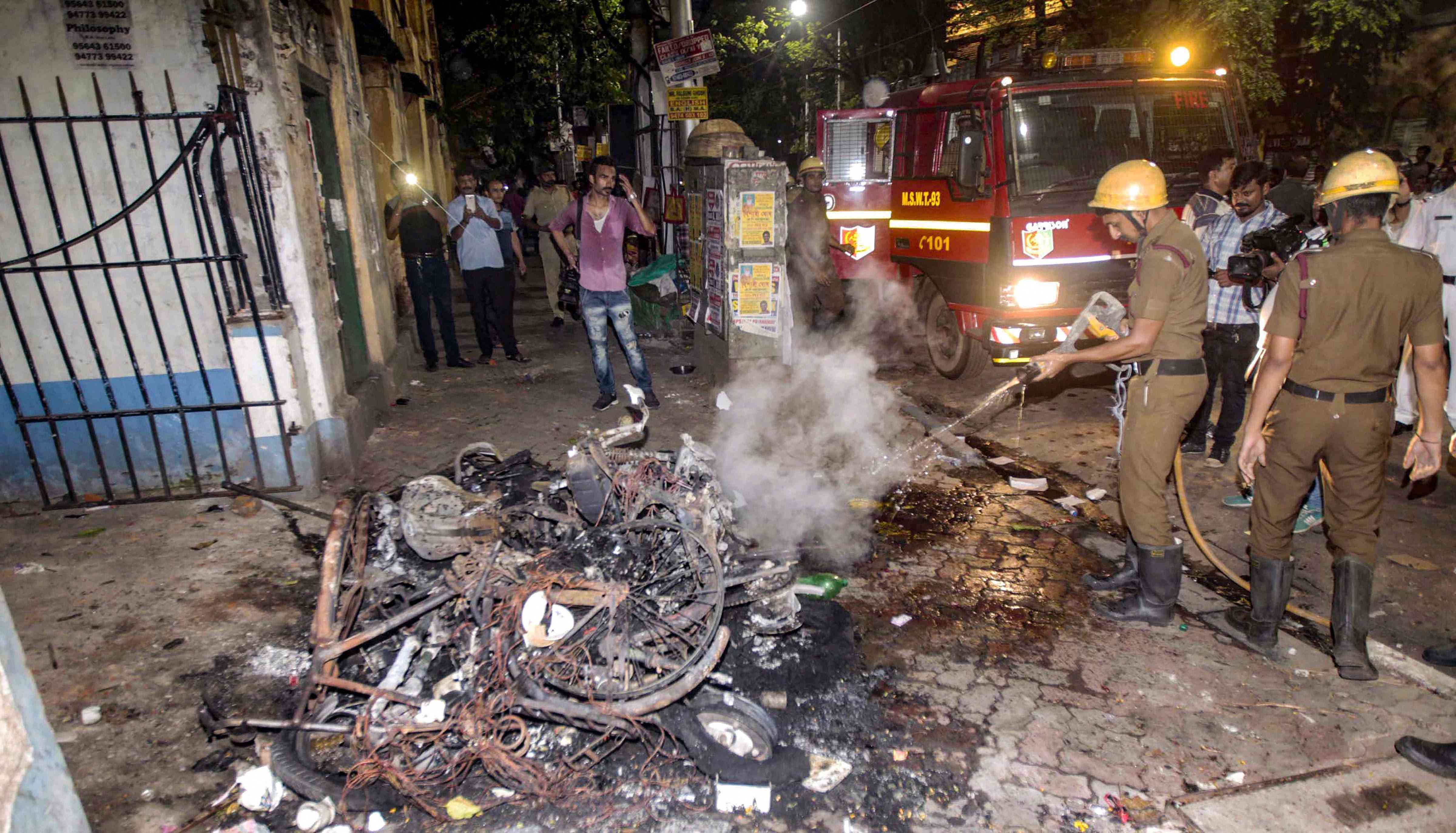 Firefighters douse vehicles set afire by BJP supporters in Kolkata on May 14. Credit: PTI