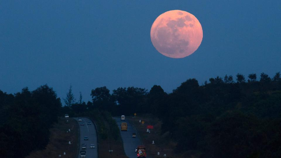 The supermoon rises over a highway near Yangon, Myanmar, on Sunday. (Photo credit: AFP)