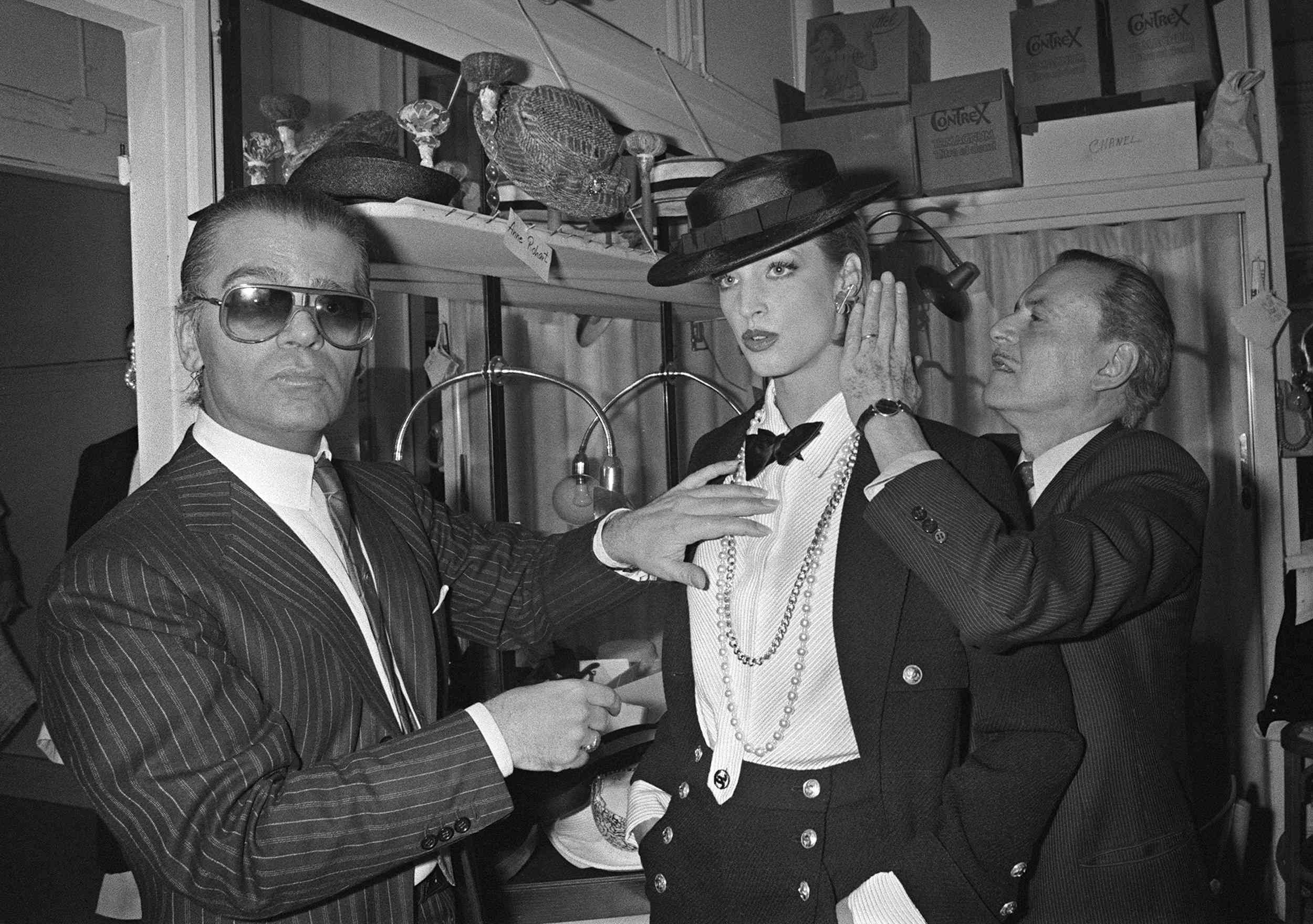 German fashion designer Karl Lagerfeld (left) and French hairdresser Alexandre de Paris (right) prepare on January 24, 1983, a model backstage ahead of the presentation of spring-summer haute couture collection for Chanel in Paris. Photo credit: Pierre Guillaud/AFP