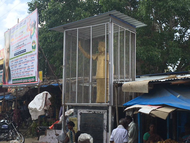 A statue of MG Ramachandran, popularly known as MGR, who left the DMK to start the AIADMK, stands in its cage.