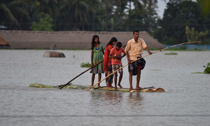 A 2016 photograph of villagers travelling on a raft in flood-affected Sildubi village in Morigoan district, 70 km from Guwahati. (Photo credit: Biju Boro/AFP).