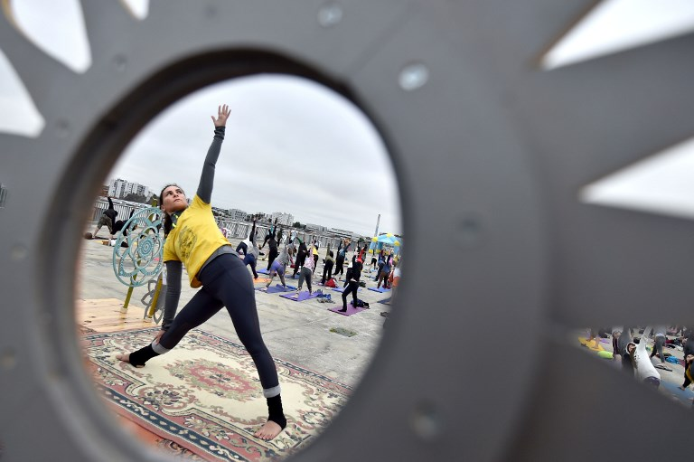 A yoga session at the sunrise organised by Nava Yoga Nantes association at a rooftop in Nantes, France. (Loic Venance/AFP)