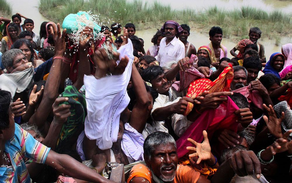 Flood victims scramble for relief material at Tila Tajpur embankment. Credit: Prashant Ravi