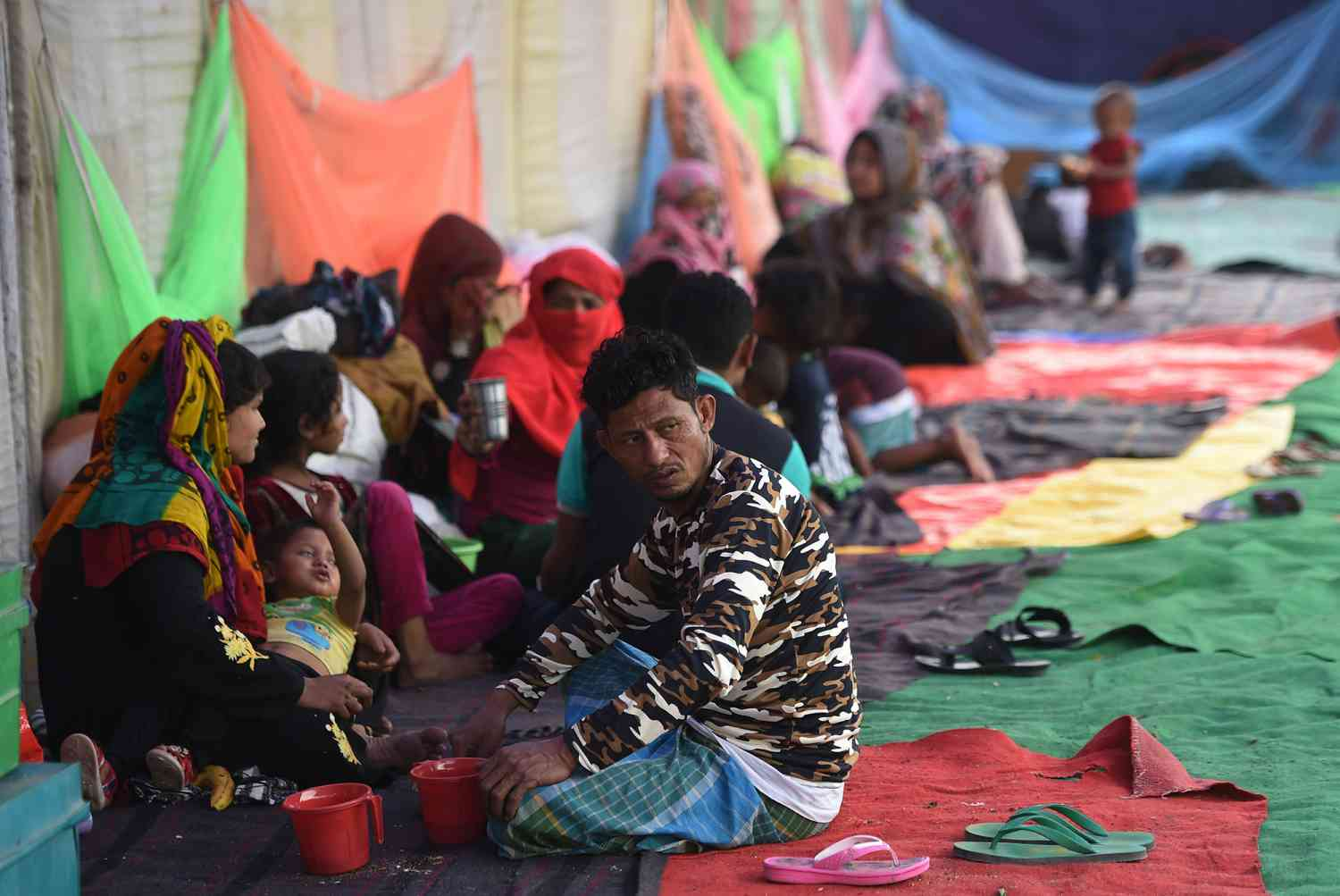 Rohingya refugees rest at a temporary shelter in New Delhi on April 16, 2018, following a fire at their refugee camp. (Photo credit: AFP).