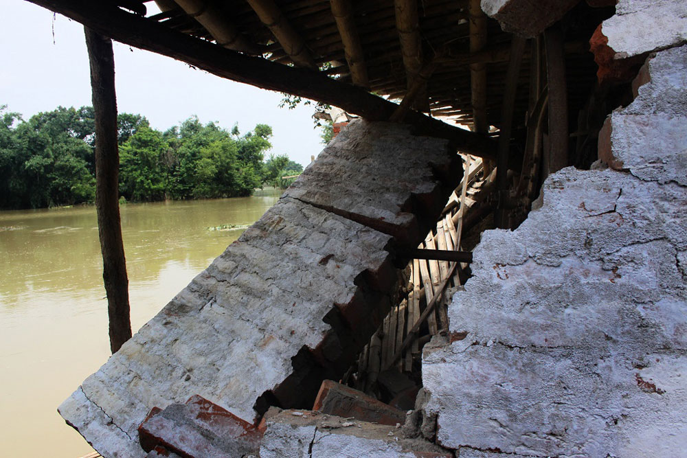 A damaged house and in backdrop the flood waters of river Bagmati. Credit: Prashant Ravi