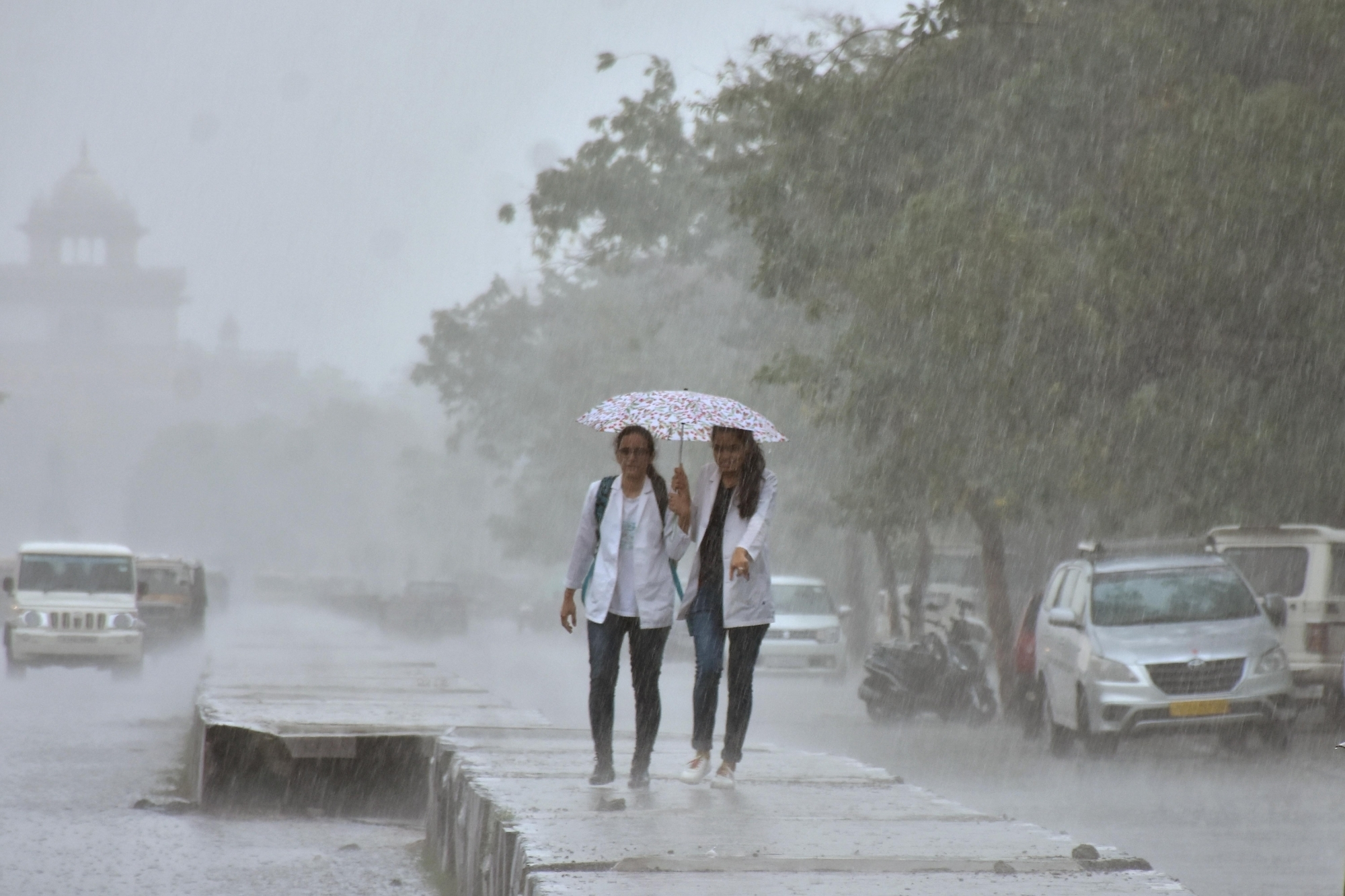 Women try to shield themselves under an umbrella as rain and strong winds lash Jaipur. (Credit: IANS)