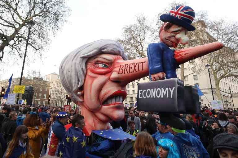A puppet head of Britain's Prime Minister Theresa May spearing a representation of the British Economy is positioned on Whitehall outside Downing Street. Image credit: Isabel Infantes / AFP