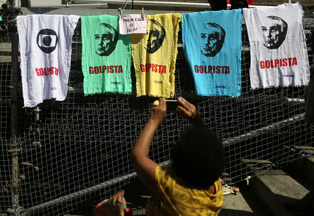 A woman hangs banners accusing Brazilian President Michel Temer of seizing power in a coup d'etat. Image credit: Pilar Olivares/Reuters
