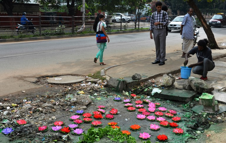 Baadal Nanjundaswamy pours paint around his art installation after placing artificial lotus flowers over a pothole filled with sewage at a pedestrian junction on Old Airport Road in Bengaluru on August 20, 2015. (Credit: Manjunath Kiran/AFP)