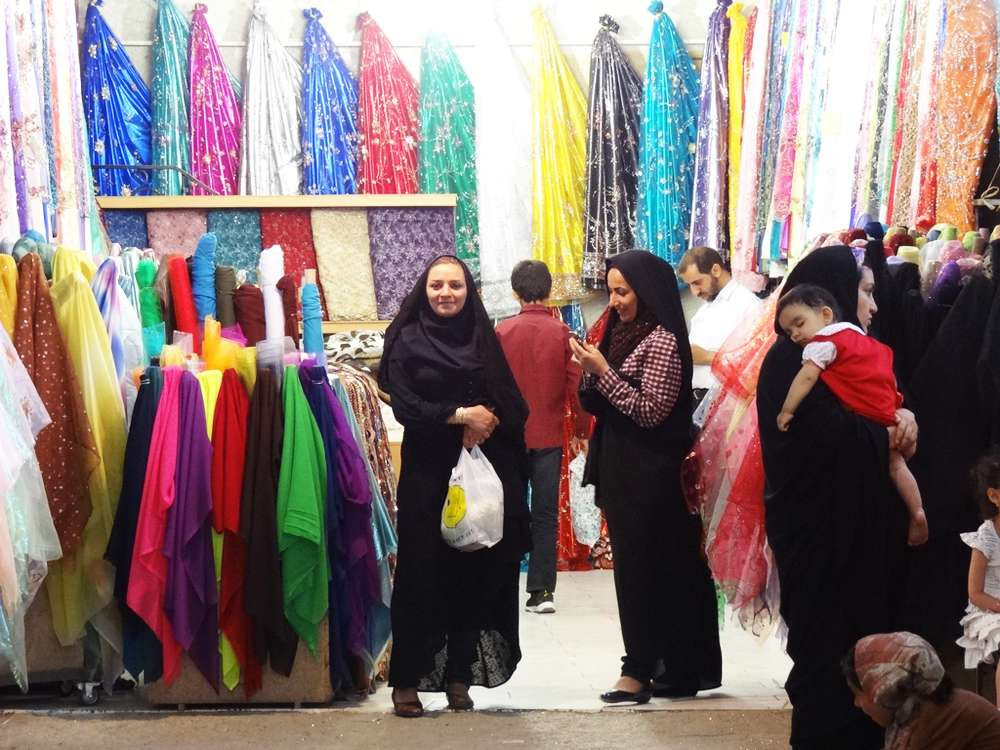 Women do their shopping near the Bazar-e-Bozorg in Tehran. Iranian women have a great taste when it comes to fashion, but when out in public they have to cover their heads either by wearing a hijab or in this case, where women are wearing a chador. A chador is a full-body-length semicircle of fabric that is open down the front. This cloth is tossed over the woman's or girl's head, but then she holds it closed in the front.