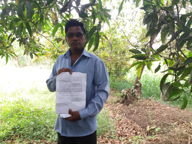 Pravin Patel, a farmer from Valsad's Endergotta village, holds up the land acquisition notification he received.
