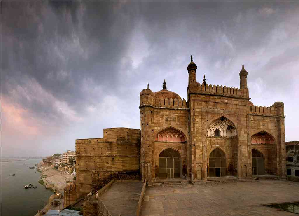 Alamgir's Mosque: The most prominent Mughal monument in the holy city of Banaras is this mosque that emperor Aurangzeb erected in 1669. Built on a terrace high above Panchaganga Ghat, it can be reached by a steep flight of steps from the river below. The vertical proportions of the prayer hall's triple-bayed facade were once accentuated by a pair of slender corner minarets that rose 50 metres above the terrace, but they do not exist any longer. Battlements conceal three domes of almost equal height, chhatris (elevated dome-shaped pavilions) at the rear corners serve as lookouts. The interior, which comprises a line of only three chambers, is roofed by domes with intricate plaster decoration.