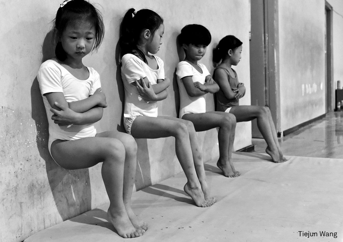 Daily Life, second prize (singles) | Sweat Makes Champions: Four students of a gymnastics school in Xuzhou, China, do toe-pressure training for 30 minutes in the afternoon. (Tiejun Wang, China)