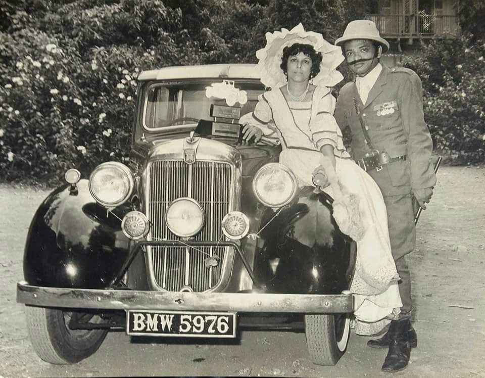 Kersi with wife during a Parsi dress competition standing next to their vintage Morris.