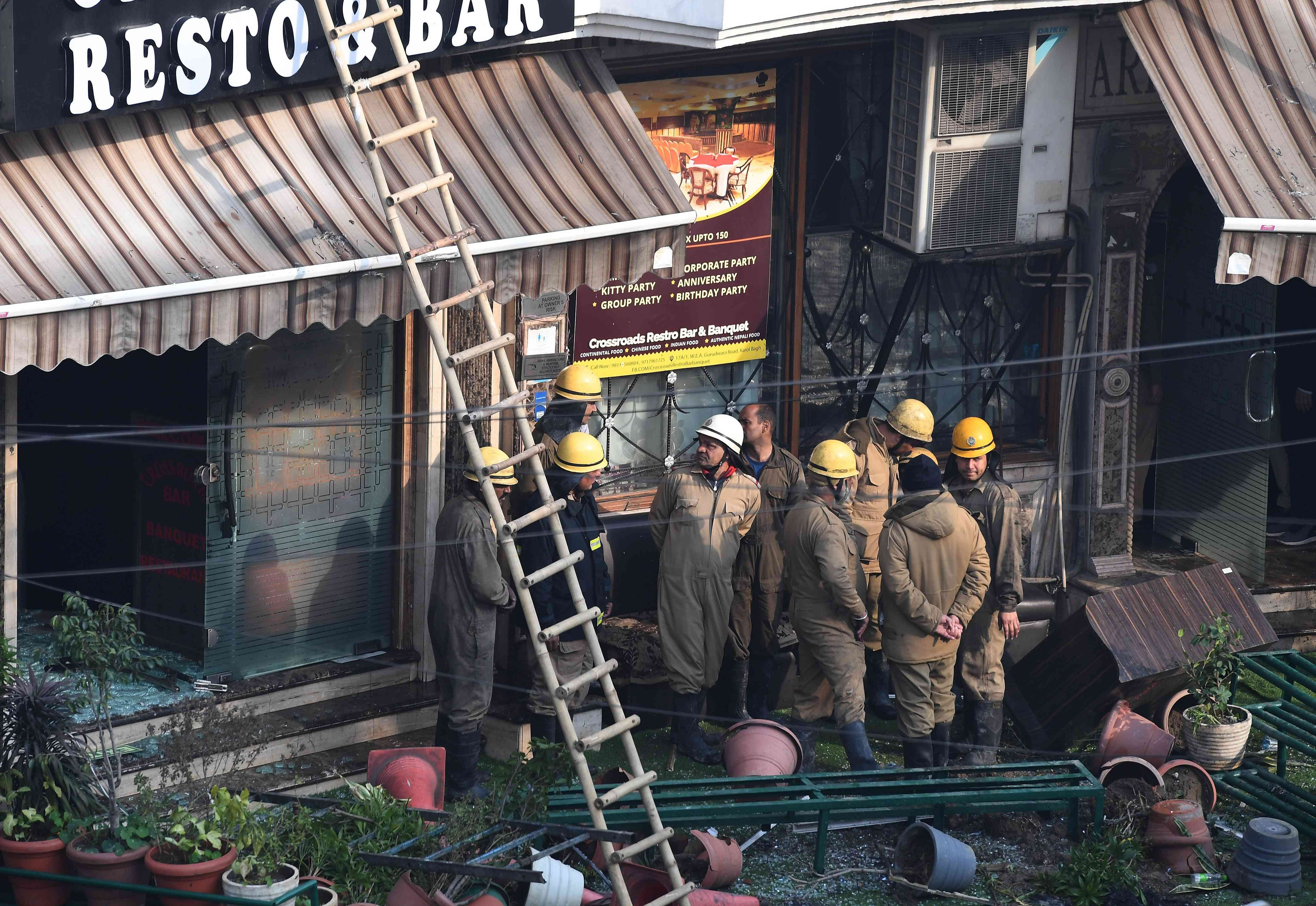 Delhi Fire Services and Delhi police personnel stand outside Hotel Arpit Palace after the fire was extinguished. (Photo credit: AFP)
