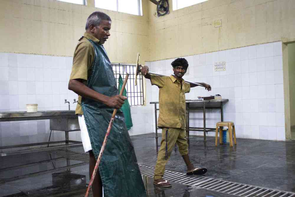 Sanitation workers mop a mortuary's floor.