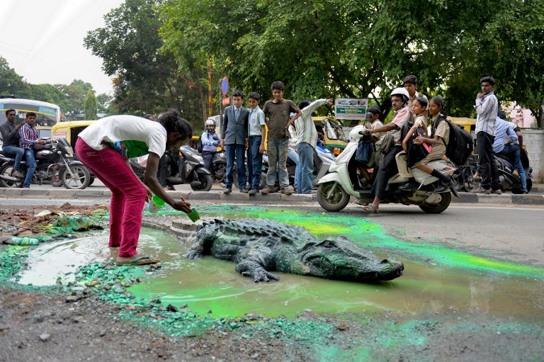 Baadal Nanjundaswamy paints and places a life-size model of a crocodile into a huge water-logged pothole in Bengaluru Sultanpalya traffic junction on June 18, 2015. (Credit: Manjunath Kiran/AFP)