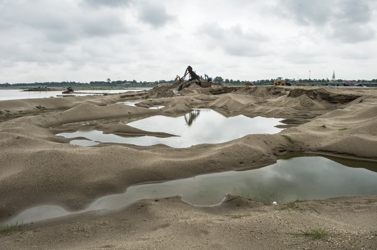 Piles of sand created by extraction along the Mekong River in Vientiane in May 2016. Grain by grain, truckload by truckload, Laos' section of the Mekong river is being dredged of sand to make cement – a commodity being devoured by a Chinese-led building boom in the Laos capital. (Photo credit: Lillian Suwanrumpha/AFP).