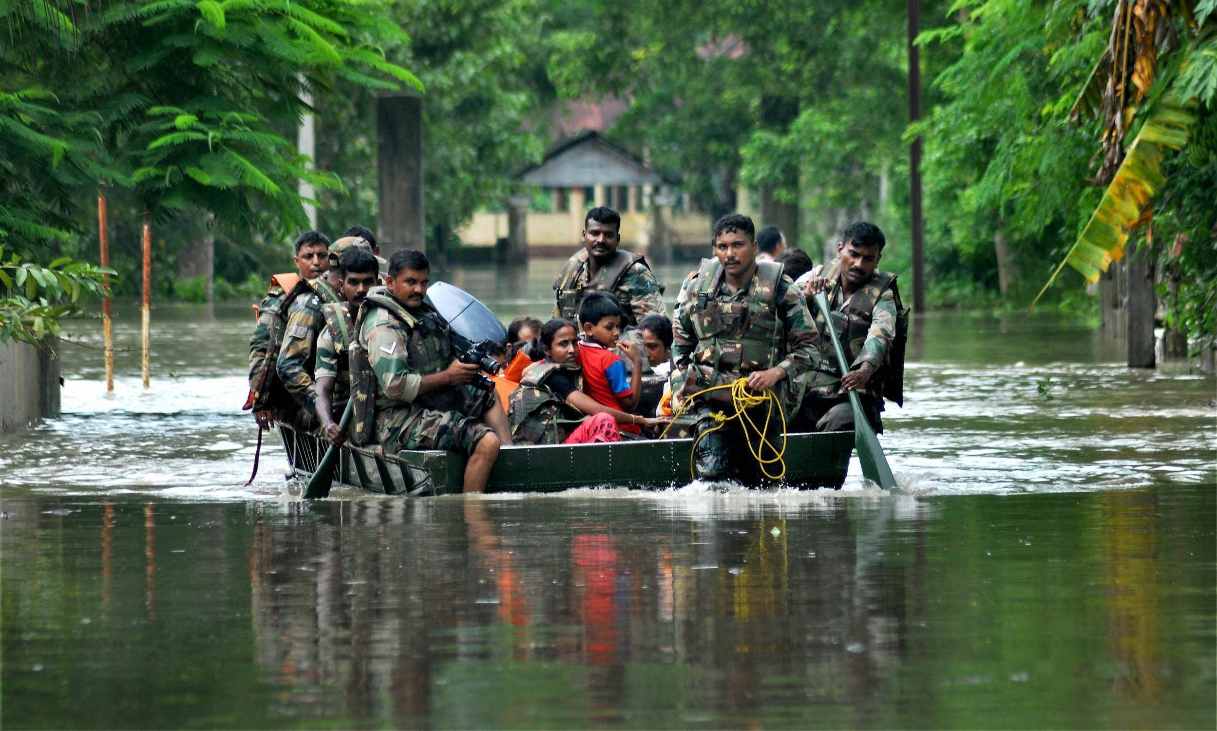Rescue personnel in a flood-affected village in the Nagaon district of Assam on Sunday. PTI Photo