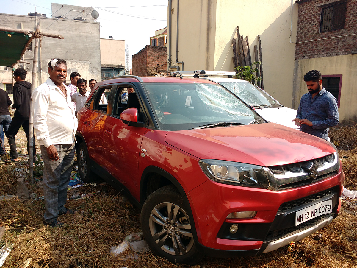 Bhausaheb Dherange and Ganesh Dherange stand next to their car, whose windows and windshields were smashed on January 1. Photo: Mridula Chari